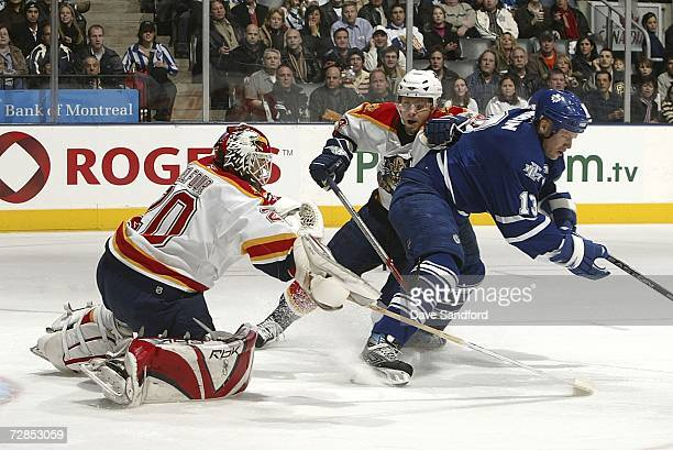 Ed Belfour of the Florida Panthers stops Mats Sundin of the Toronto Maple Leafs as Ruslan Salei of the Florida Panthers looks on during their NHL...