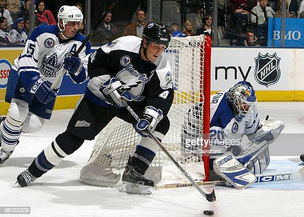 Ed Belfour of the Toronto Maple Leafs gets into position to make a save as Vincent Lecavalier of the Tampa Bay Lightning attempts a wrap around...