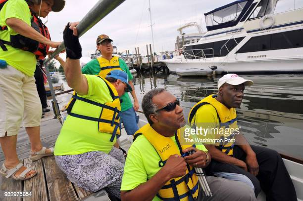 Ed Bordley bottom right center adjusts his life jacket as he Eric Phifer right and other members of Out of Sight Dragons prepare to launch their boat...