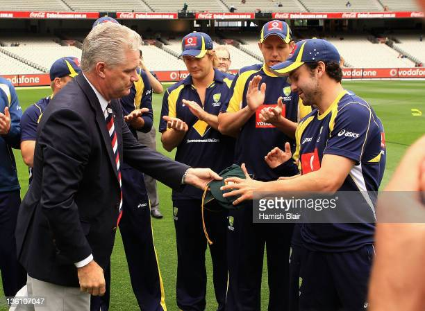 Ed Cowan of Australia is presented with his Baggy Green Cap by former cricketer Dean Jones day one of the First Test match between Australia and...
