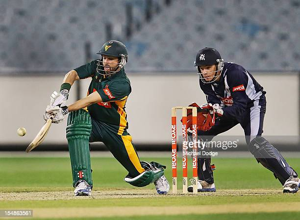 Ed Cowan of the Tigers bats as wicketkeeper Peter Handscomb of the Bushrangers looks on during the Ryobi One Day Cup match between Victorian...