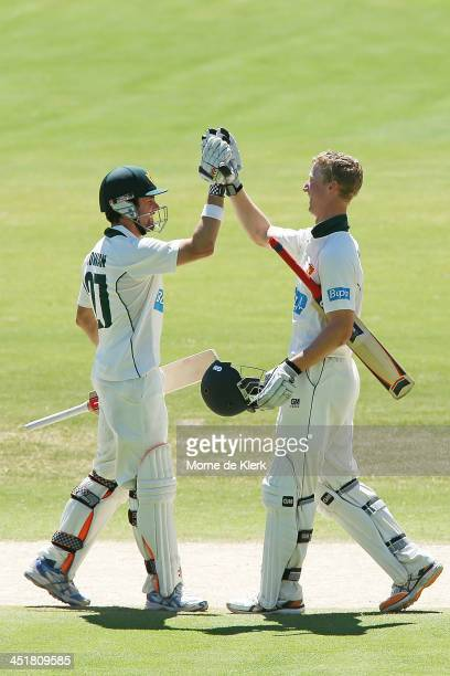 Ed Cowan of the Tigers congratulates teammate Jordan Silk after he reached 100 runs during day four of the Sheffield Shield match between the South...