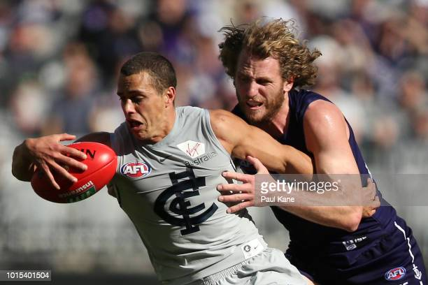 Ed Curnow of the Blues gathers the ball against David Mundy of the Dockers during the round 21 AFL match between the Fremantle Dockers and the...