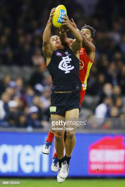 Ed Curnow of the Blues marks the ball against Aaron Hall of the Suns during the round four AFL match between the Carlton Blues and the Gold Coast...