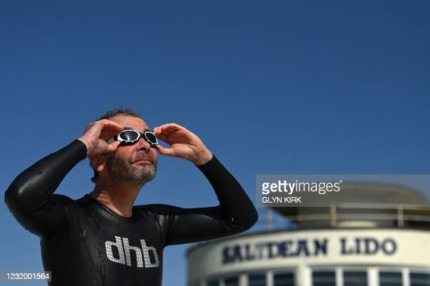 Ed Curtis poses for a photograph after swimming at Saltdean Lido near Brighton as England's third Covid-19 lockdown restrictions ease, allowing...