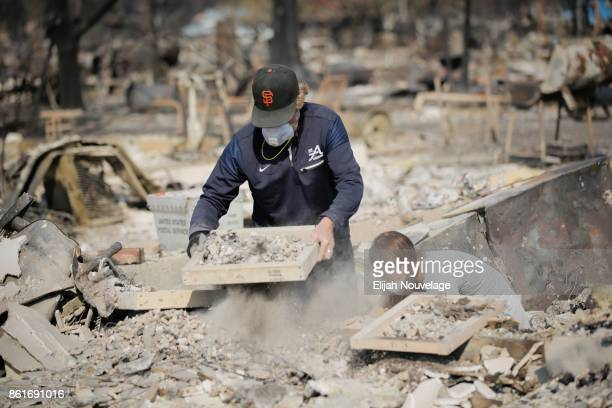 Ed Curzon and his daughter Margaret use sifting trays donated by the Boy Scouts of America to search through the remains of his home for items of...
