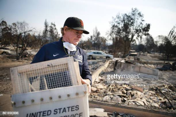 Ed Curzon carries sifters to search through the remains of his home for items of emotional importance in the Coffey Park neighborhood on Oct 15 2017...