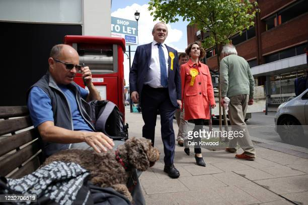 Ed Davey, Leader of the Liberal Democrats and Luisa Porritt, Liberal Democrat Mayoral Candidate walk past a man on a bench with a dog as they...