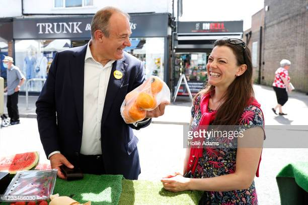 Ed Davey, Leader of the Liberal Democrats gestures with a bag of oranges at Sarah Green, candidate for Chesham and Amersham, while out canvassing on...