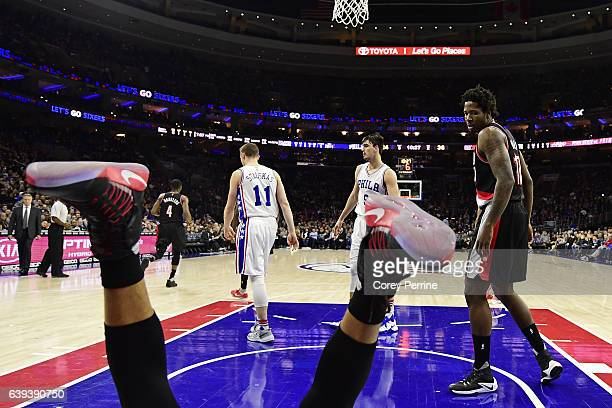 Ed Davis of the Portland Trail Blazers looks onto the upright legs of teammate CJ McCollum after loosing his footing against the Philadelphia 76ers...