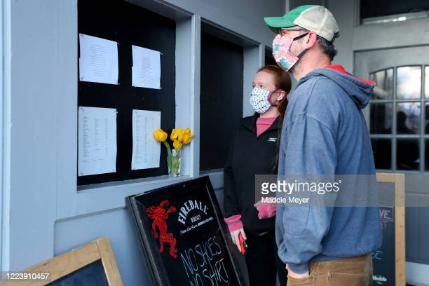Ed Day and Sara Gilman read the take out menu at the Speakeasy Bar and Grill on May 09, 2020 in Newport, Rhode Island. Non-critical retail...
