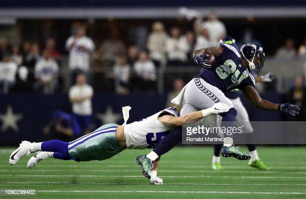 Ed Dickson of the Seattle Seahawks is tackled by Leighton Vander Esch of the Dallas Cowboys in the second quarter of the Wild Card Round at ATT...