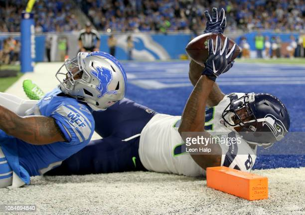 Ed Dickson of the Seattle Seahawks scores a touchdown against Quandre Diggs of the Detroit Lions during the second quarter at Ford Field on October...