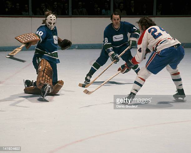 Ed Dyck of the Vancouver Canucks saves a shot taken by Chuck Lefley of the Montreal Canadiens Circa 1970 at the Montreal Forum in Montreal Quebec...