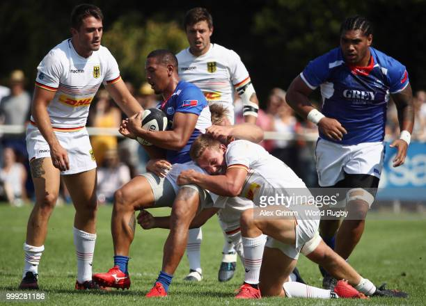 Ed Fidow of Samoa is challenged by Hagen Schulte and Jacobus Otto of Germany during the Germany v Samoa Rugby World Cup 2019 qualifying match on July...