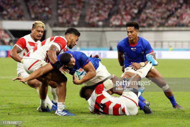Ed Fidow of Samoa is tackled by Timothy Lafaele and Kotaro Matsushima of Japan during the Rugby World Cup 2019 Group A game between Japan and Samoa...