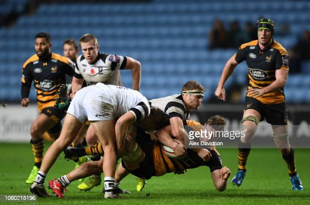 Ed Holmes and Sam Bedlow of Bristol Bears tackle Will Rowlands of Wasps during the Premiership Rugby Cup match between Wasps and Bristol Rugby at...
