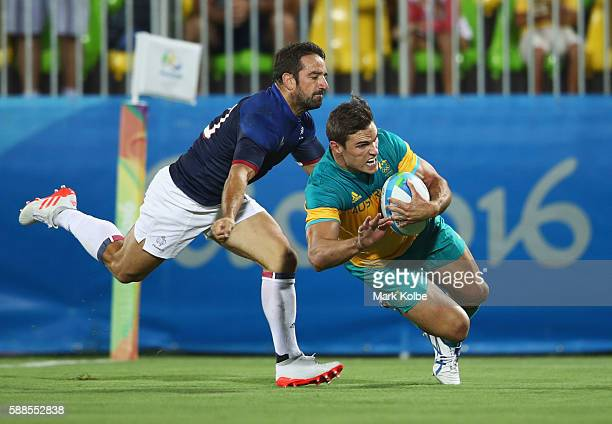 Ed Jenkins of Australia holds off Julien Candelon of France to score a try during the Men's Rugby Sevens placing 78 match between France and...
