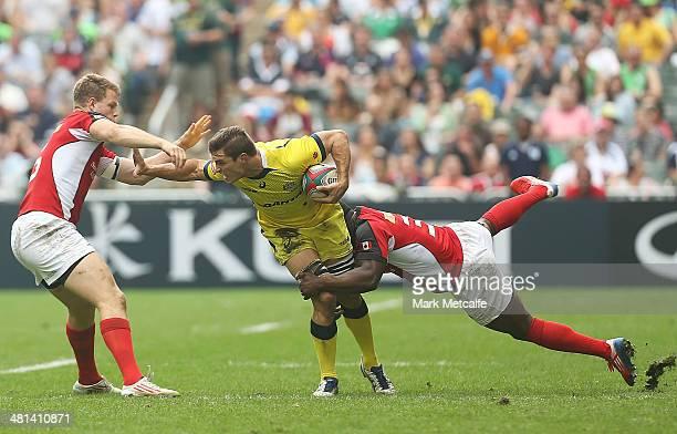 Ed Jenkins of Australia is tackled during the Cup quarterfinal match between Australia and Canada during day three of the 2014 Hong Kong Sevens at...
