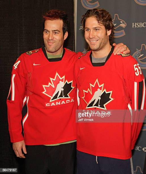 Ed Jovanovski and Todd Bertuzzi of th eVancouver Canucks embrace after being presented with their Team Canada Olympic jerseys prior to the game...