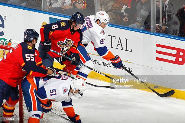 Ed Jovanovski of the Florida Panthers checks Frans Nielsen of the New York Islanders out of the crease as Tim Kennedy and Kyle Okposo fight for...