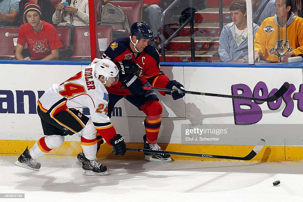 Ed Jovanovski #55 of the Florida Panthers tangles with Jiri Hudler #24 of the Calgary Flames at the BB&T Center on April 4, 2014 in Sunrise, Florida.