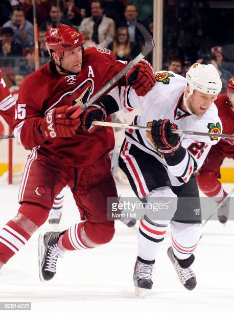 Ed Jovanovski of the Phoenix Coyotes and Cam Barker of the Chicago Blackhawks chase after a loose puck on November 5 2009 at Jobingcom Arena in...