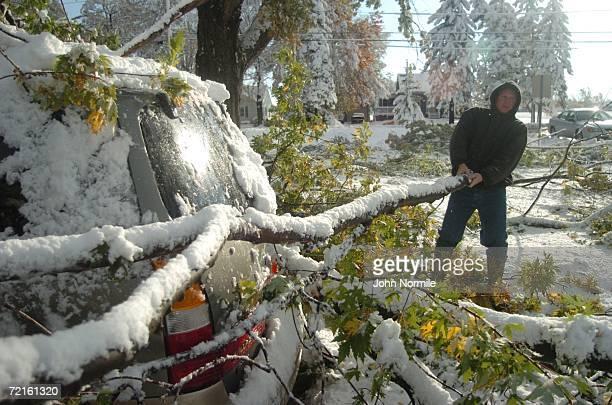 Ed Kawalek clears debris that fell on a car October 13, 2006 outside of Buffalo in Hamburg, New York. A rare and record breaking early season...