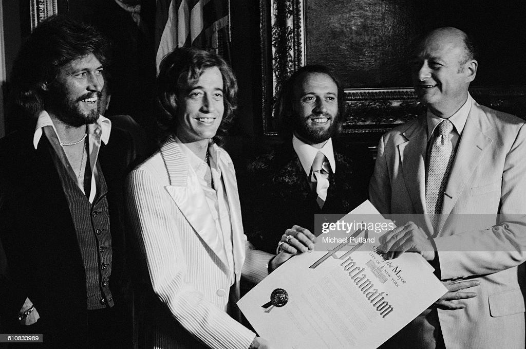 Ed Koch (1924 - 2013), Mayor of New York City, presents his office's proclamation of 'Disco Week' in New York, to pop vocal trio The Bee Gees, USA, September 1978. The group presented Koch with a framed platinum disc. Left to right: Barry Gibb, Robin Gibb (1949 - 2012), Maurice Gibb (1949 - 2003) and Ed Koch.