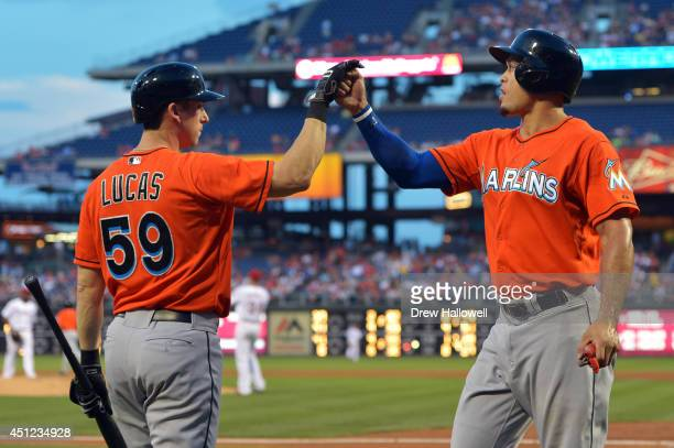 Ed Lucas of the Miami Marlins congratulates teammate Giancarlo Stanton after scoring a run in the fourth inning against the Philadelphia Phillies at...