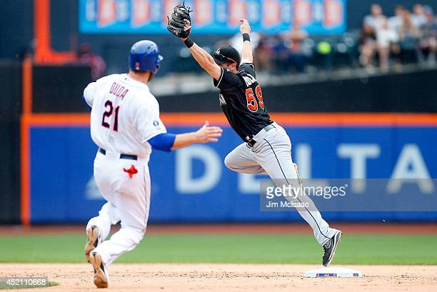 Ed Lucas of the Miami Marlins is pulled of the bag as Lucas Duda of the New York Mets is safe at second base during the eighth inning at Citi Field...