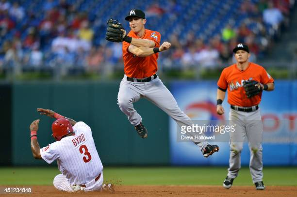 Ed Lucas of the Miami Marlins jumps through the air after striking out Marlon Byrd of the Philadelphia Phillies at second base in the fourth inning,...
