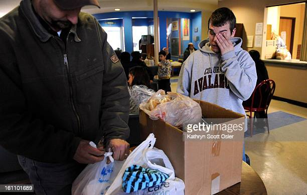 HUNGRY_KSO_2_2_09157 Ed Michel left helps his son Tim Michel pack a few bags of bread and baby diapers in a box on Monday at the Jeffco Action Center...