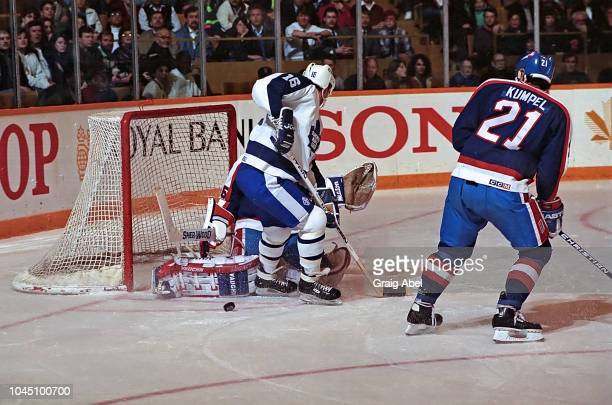 Ed Olczyk of the Toronto Maple Leafs skates against Bob Essensa and Mark Kumpel of the Winnipeg Jets during NHL game action on March 17 1990 at Air...