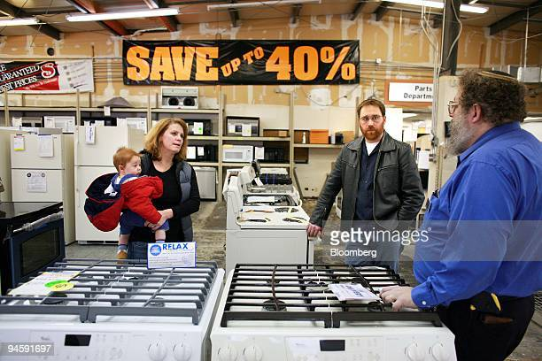 Ed Pollak right a product specialist shows Andrea Evans her husband Garrett Evans and their seven month old son Ivan Evans different options in...