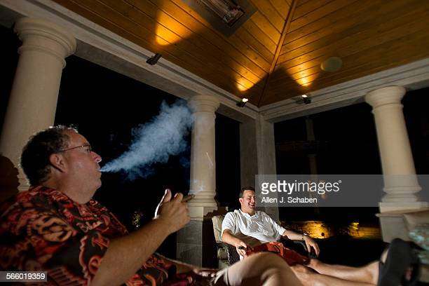 """Ed Richmond, left, and Eddie Antonini hang out, smoke cigars and have drinks in Ed Richmond's """"man cave """" while watching the Dodgers game at his La..."""