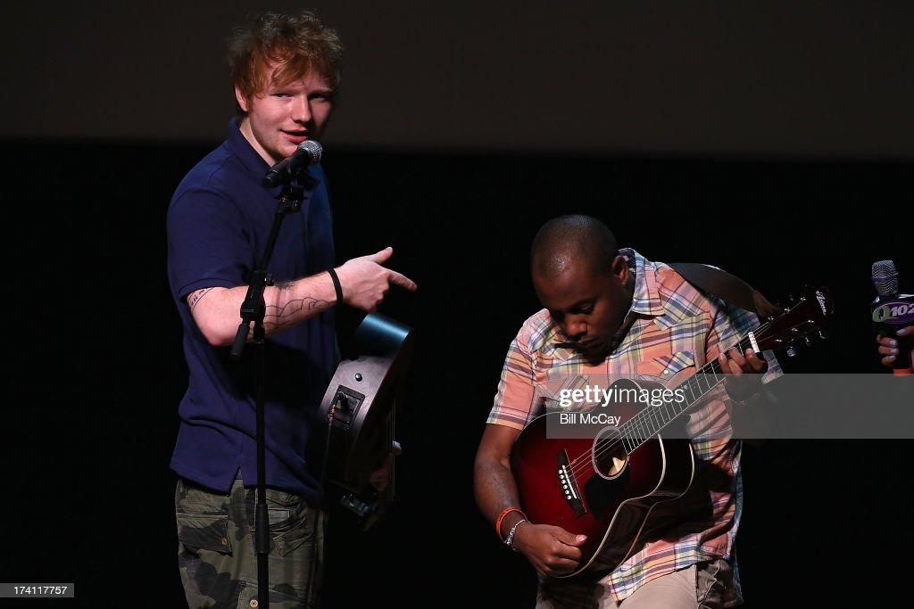 Ed Sheeran teaches Q102 Radio personality Maxwell how to play the guitar at the Philadelphia Museum of Art July 20, 2013 in Philadelphia, Pennsylvania.