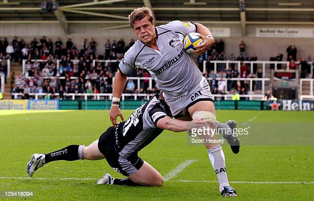 Ed Slater of Leicester evades the challenge from James Fitzpatrick of Newcastle to score their first try during the AVIVA Premiership match between...