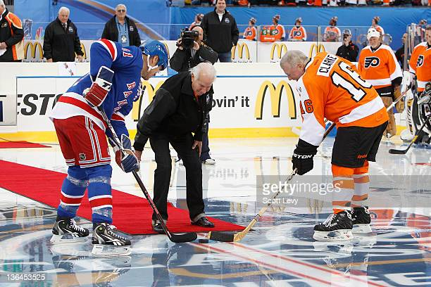 Ed Snider Chairman of the Philadelphia Flyers drops the honorary puck between Bob Clarke of the Philadelphia Flyers and Mark Messier of the New York...