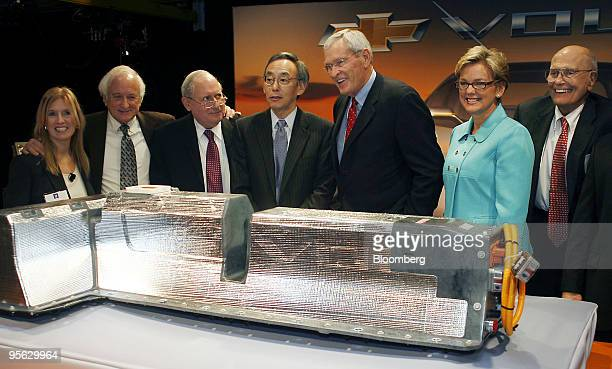 Ed Whitacre chief executive officer of General Motors Co third from right poses with other attendees behind a lithiumion battery during a news...