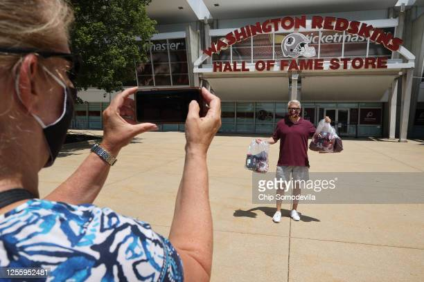 Ed Zierle of Annapolis, Maryland, poses for his wife Wendy Zierle with his bags of newly purchased merchandise from the Washington Redskins Hall of...