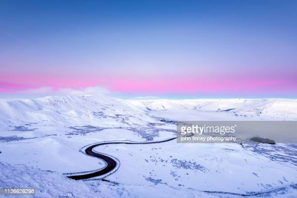 edale valley snowy winding road, pink dawn. peak district. uk - polar stock pictures, royalty-free photos & images