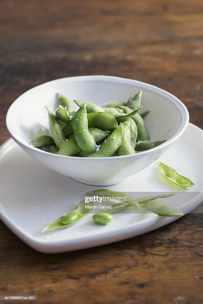 Edamame with salt in bowl on wood table : Stockfoto