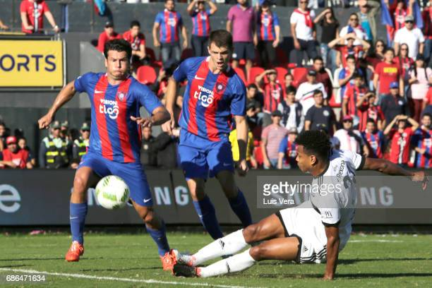 Edcarlos Conceicao of Olimpia fights for the ball with Nelson Haedo Valdez and Joel Jimenez of Cerro Porteño during a match between Olimpia and Cerro...