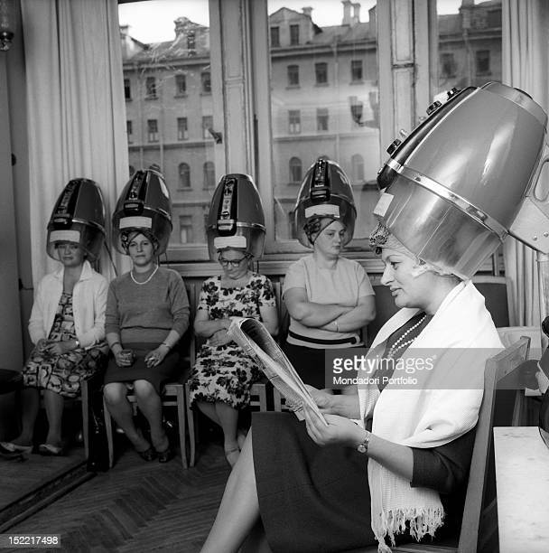 Edda Vincenzi at the hairdresser's she is sat down and is reading a Russian newspaper Moscow September 1964