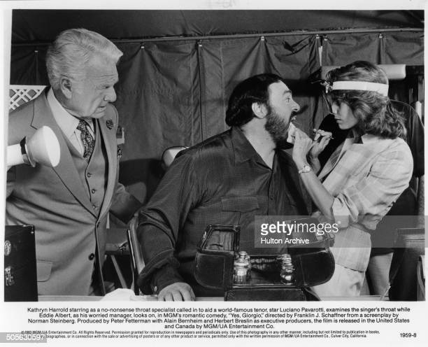 Eddie Albert looks on as Luciano Pavarotti has his throat checked by Kathryn Harrold in a scene from the movie Yes Giorgio circa 1982