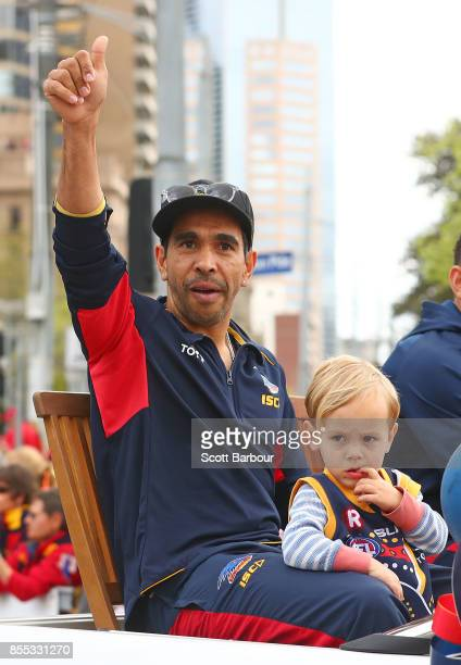 Eddie Betts of the Crows and his son Lewis Betts wave to the crowd during the 2017 AFL Grand Final Parade ahead of the Grand Final between the...