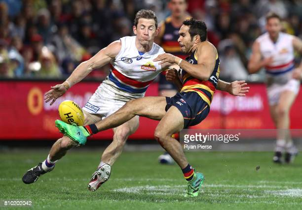 Eddie Betts of the Crows gets a kick away despite pressure from Dale Morris of the Bulldogs during the round 16 AFL match between the Adelaide Crows...