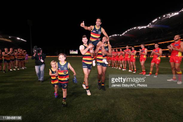 Eddie Betts of the Crows is chaired of by team mates Bryce Gibbs and Cameron EllisYolmen after his 300th game during the 2019 AFL round 05 match...