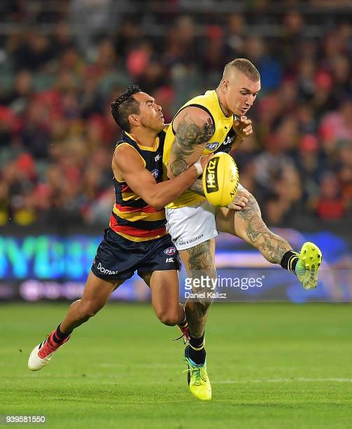 Eddie Betts of the Crows tackles Dustin Martin of the Tigers during the round two AFL match between the Adelaide Crows and the Richmond Tigers at...